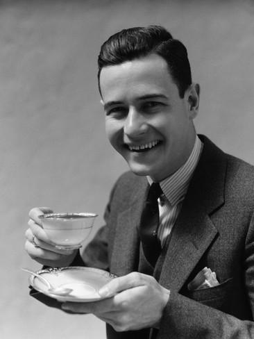 h-armstrong-roberts-man-wearing-suit-smiling-drinking-coffee-from-china-cup-and-saucer.